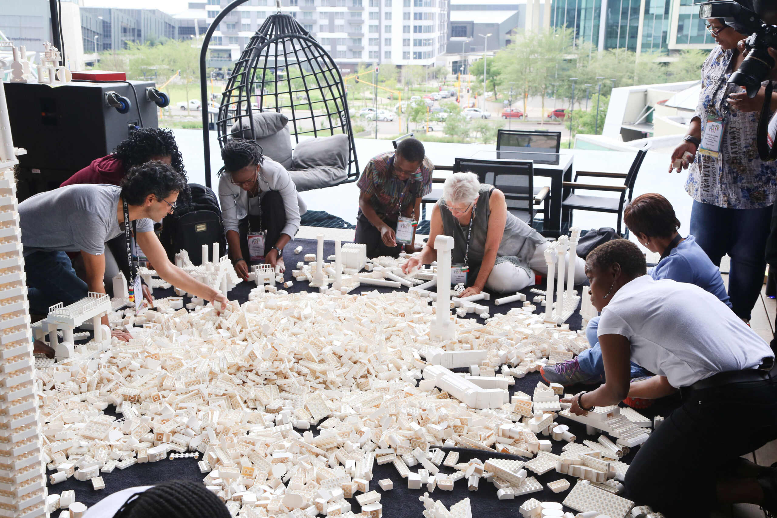 People building bridges with a giant pile of white DUPLO